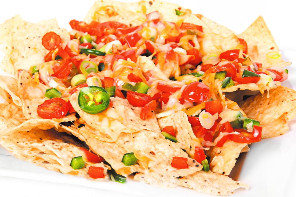Deliciosos nachos caseros bañados en queso cheddar, pollo desmenuzado y vegetales.